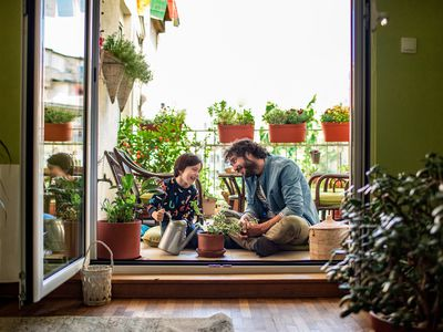 Father and young son watering plants on the terrace