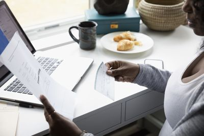 Woman holding check and a statement paying monthly bills at a desk