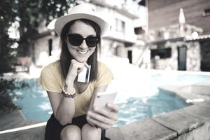 A woman sits in the shade near a sparkling swimming pool holding a credit card and using a smartphone