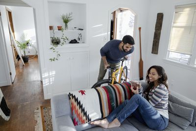 Couple in Living Room With Man on Bicycle and Woman on Couch Using Smartphone