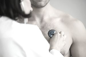 Female doctor checking heart rate of male patient