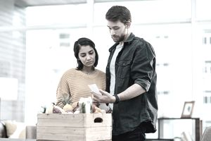 Shot of a young couple going through their receipts at home after buying groceries.