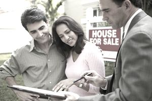 A young couple speaking to a realtor about selling their home