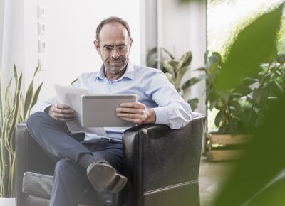 person in suit sitting in chair reading paperwork on his tablet