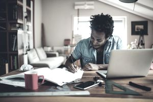 Young man writing a business plan in home office