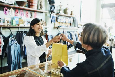 A woman buys jewelry from a boutique in her new neighborhood.