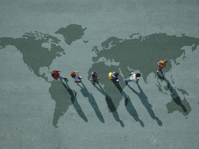 People walking in line across world map, painted on asphalt, front person walking left