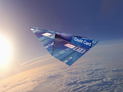 Credit card folded into paper airplane in atmosphere