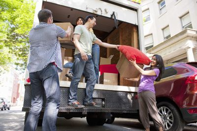 Group of friends unloading boxes out of moving truck that they obtained with rental truck insurance