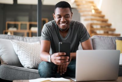 Man working on smart phone and laptop from couch