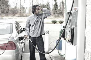 Photo of a young man watching filling his gas tank.