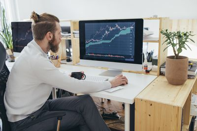 Young entrepreneur analyzing a financial stock market graph at work