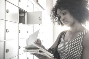 Woman with curly hair and dark skin stands at a wall of metal mailboxes, sifting through her mail.