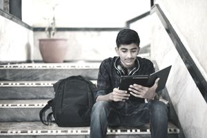 College student studying and using digital tablet while sitting on stairway.