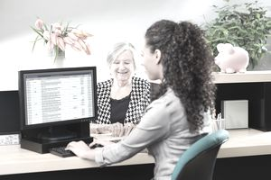 A customer at a banking window checking the maturity of her CD account a with bank teller