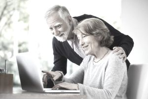 A senior couple at home using a computer.