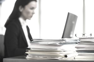 Woman at computer with stack of files on desk