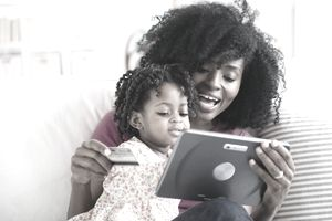 Mother and toddler shopping online with credit card