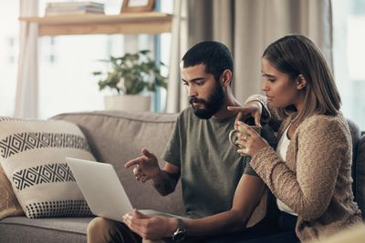 Two people sitting close together on couch looking at computer