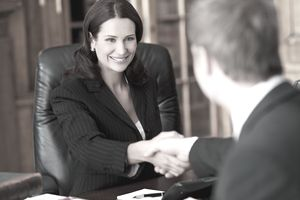 Two people shake hands upon completing a real estate transaction