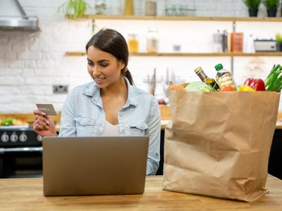 Woman standing in a kitchen looking at her credit card, next to a bag of groceries.