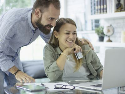 Couple looking at computer in their house, woman of the couple holding a credit card