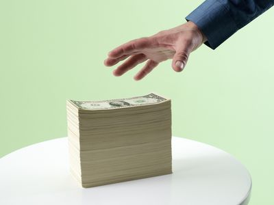 Hand reaching for stack of cash