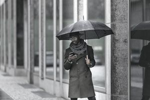 Black businessman holding an umbrella and smartphone texting in the rain.