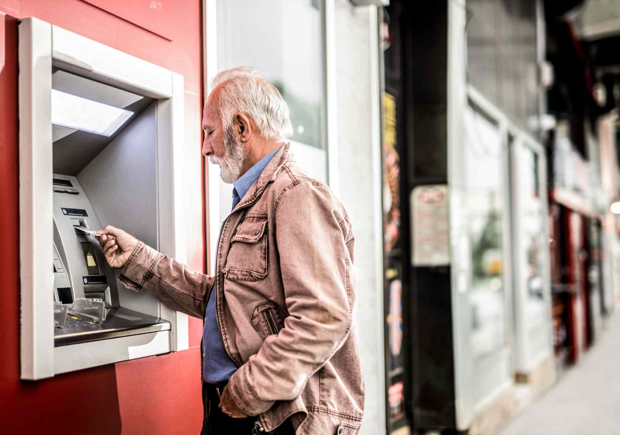 Senior man inserting a Credit Card into ATM