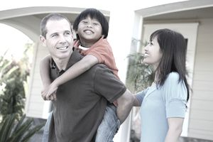Smiling couple with a child standing outside a home