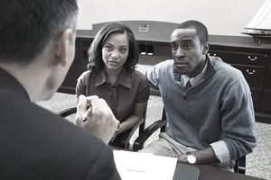 Couple talking to bank manager.