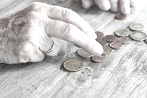 Hands of senior woman counting her retirement savings in coins