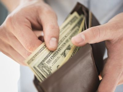 Man counting the bills in his wallet, debating whether to spend his money
