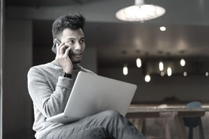 Man talking on phone with a laptop in his lap