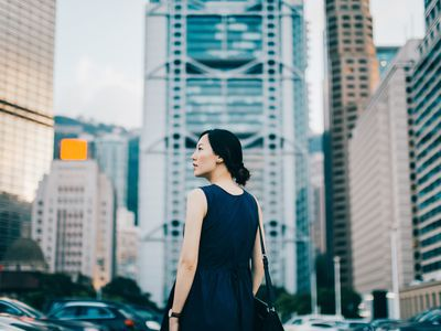 Woman looking at large buildings in city