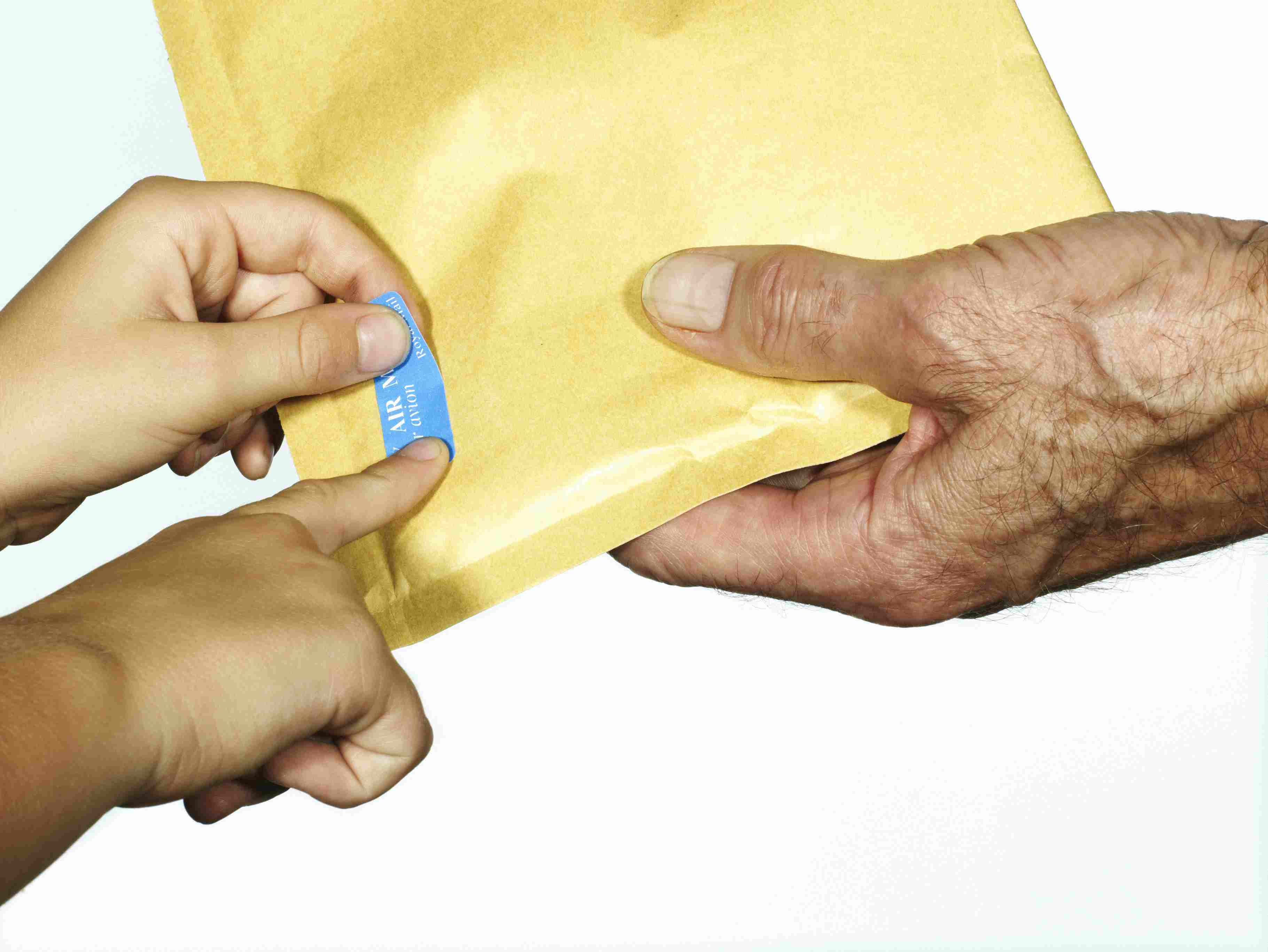 Grandfather holding Envelope and grandson pasting postage stamp