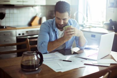 Man consulting financial paperwork with coffee at kitchen table