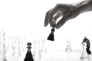 A hand making a move with chess pieces