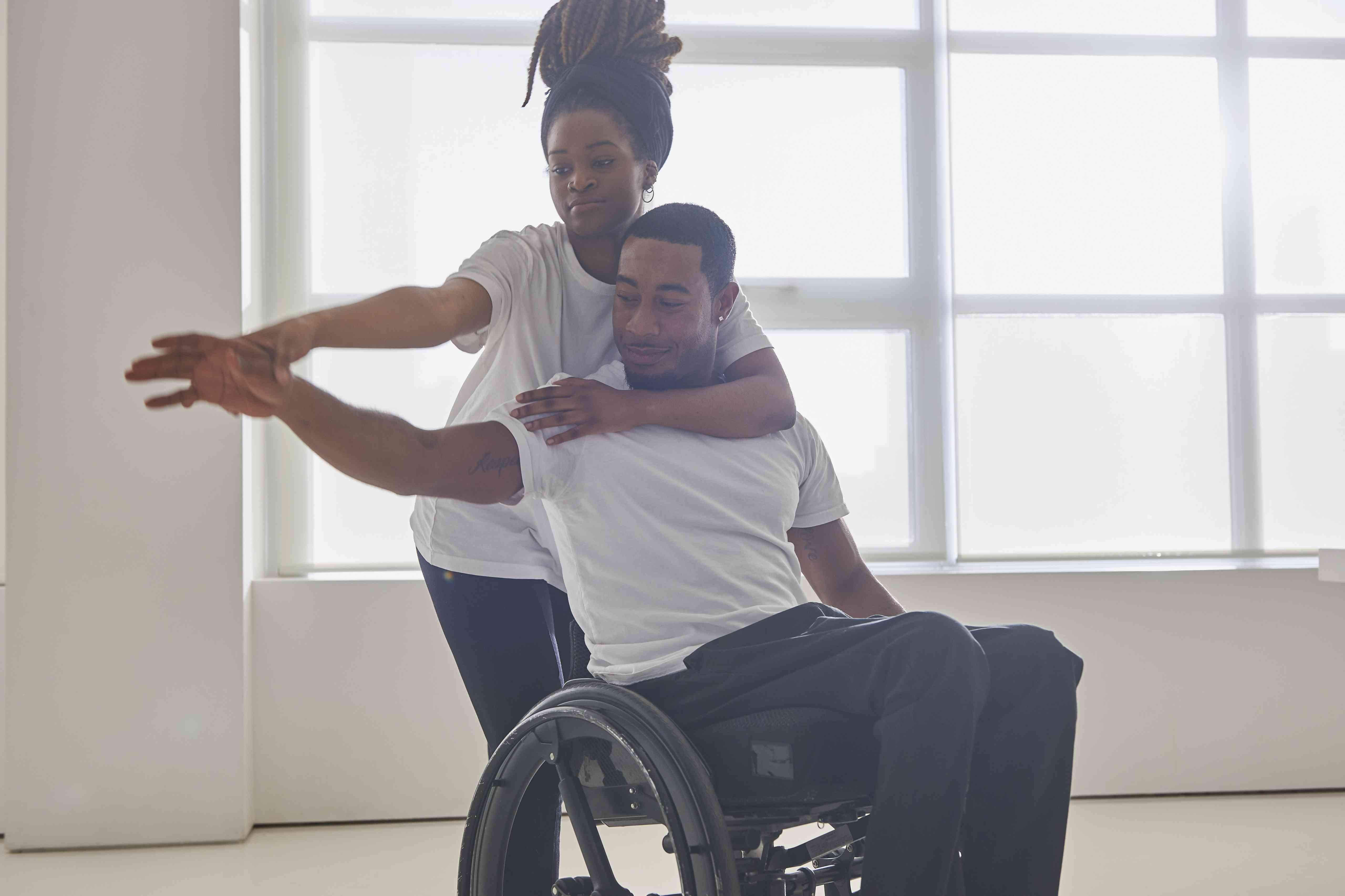 Young woman dancing together with young man in wheelchair