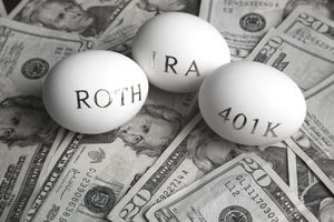Roth IRA next to 401K on pile of u.s. dollars