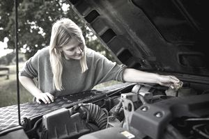 Young woman checking car with open hood