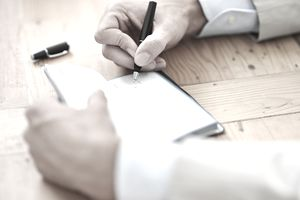 man writing in check book