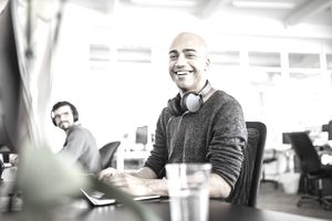 Businessman working at laptop at his desk in coworking space with man in background