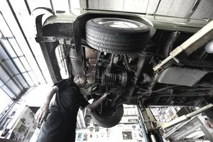 A mechanic repairing a car as it sits elevated on a lift in a garage