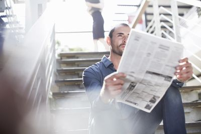 Man reading the newspaper while sitting on stairs