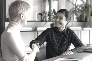 Smiling employees shake hands at office meeting