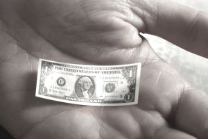 Tiny dollar bill in a hand