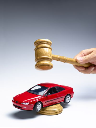 Gavel being held above a car