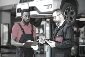 Two mechanics debate the costs of repairing a car under comprehensive car insurance.