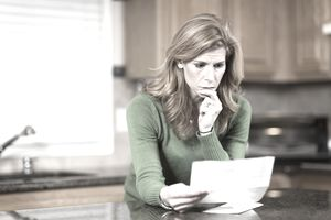 Concerned woman reading papers in her kitchen